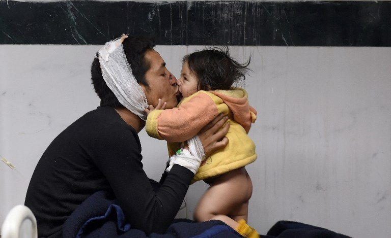 Nepalese man Suresh Parihar plays with his 8-month-old daughter Sandhaya as he is treated at a hospital in Kathmandu on April 26, 2015