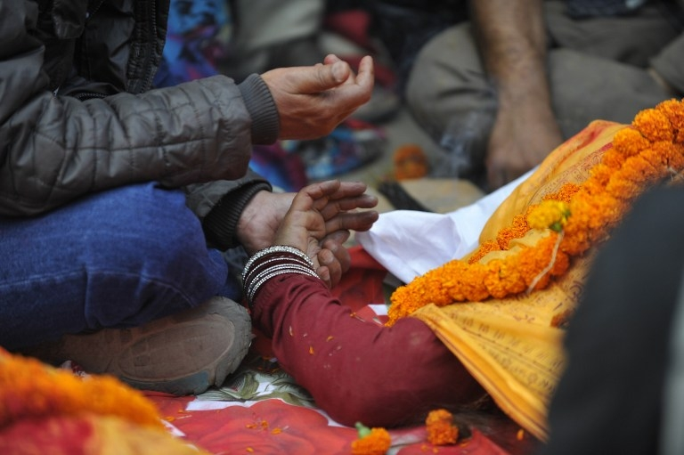 Nepalis mourn a relative at a mass cremation in Kathmandu on April 26, 2015
