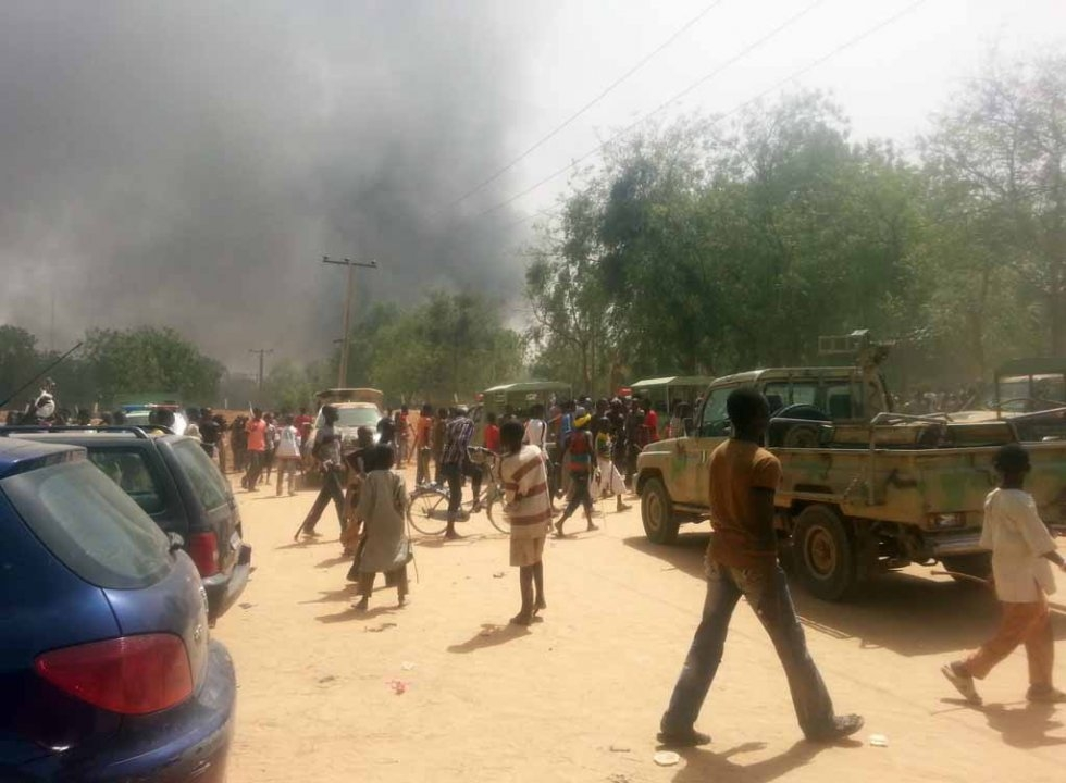 People watch smoke rise in Maiduguri in March, 2014, after Boko Haram fighters attacked a military base, freeing dozens of insurgents.