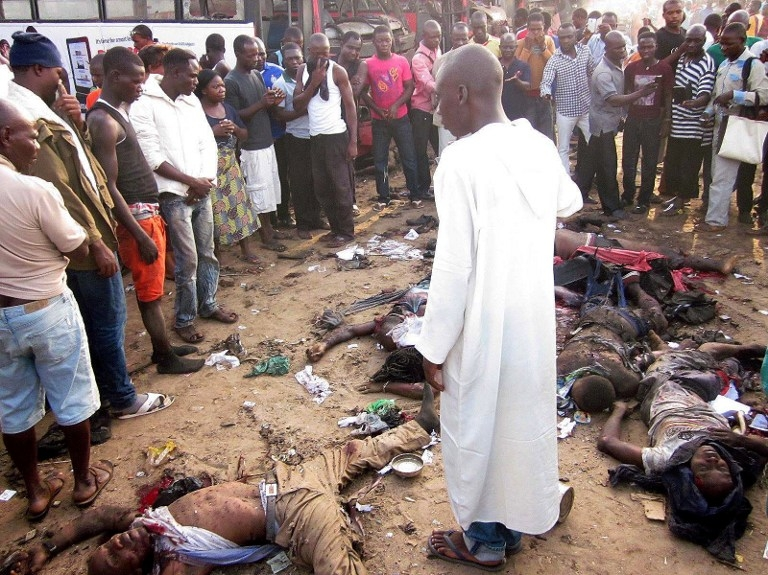 Bystanders look at dead bodies after a twin attack on a bus station in Abuja killed dozens of people on April 14, 2014