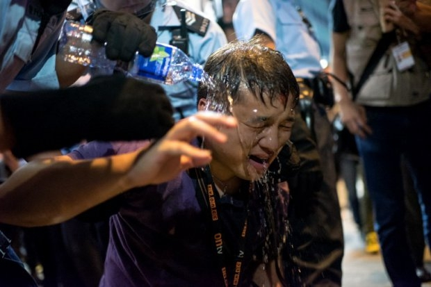 Police pour water on a local Hong Kong journalist after he was pepper sprayed in the Mongkok district of Hong Kong on October 17, 2014 (AFP Photo / Alex Ogle)