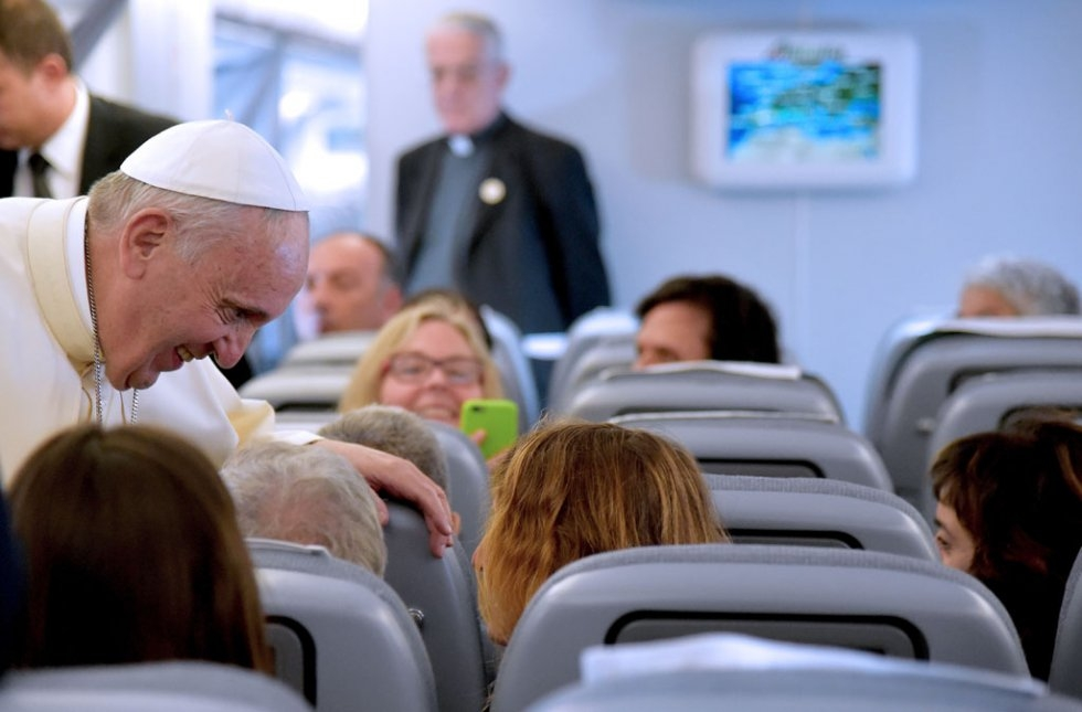Pope Francis welcomes the journalists on board a flight to Ecuador on July 5, 2015