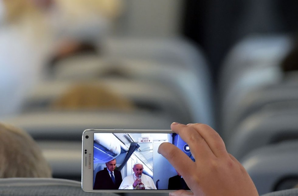 A journalist takes pictures of the Pope on a plane to Quito on July 5, 2015