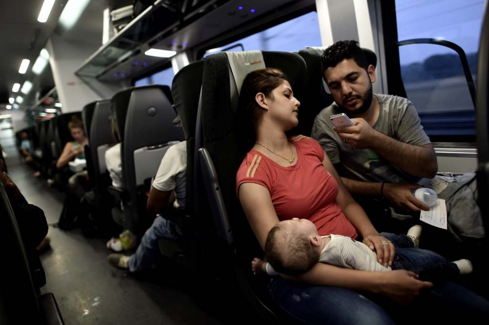 Iraqi refugees Ahmad (R) ,27 and Alia ,26, holding their four months old baby Adam, try to communicate with their family as they travel by train from Austria to Germany, on September 3 (AFP Photo / Aris Messinis)