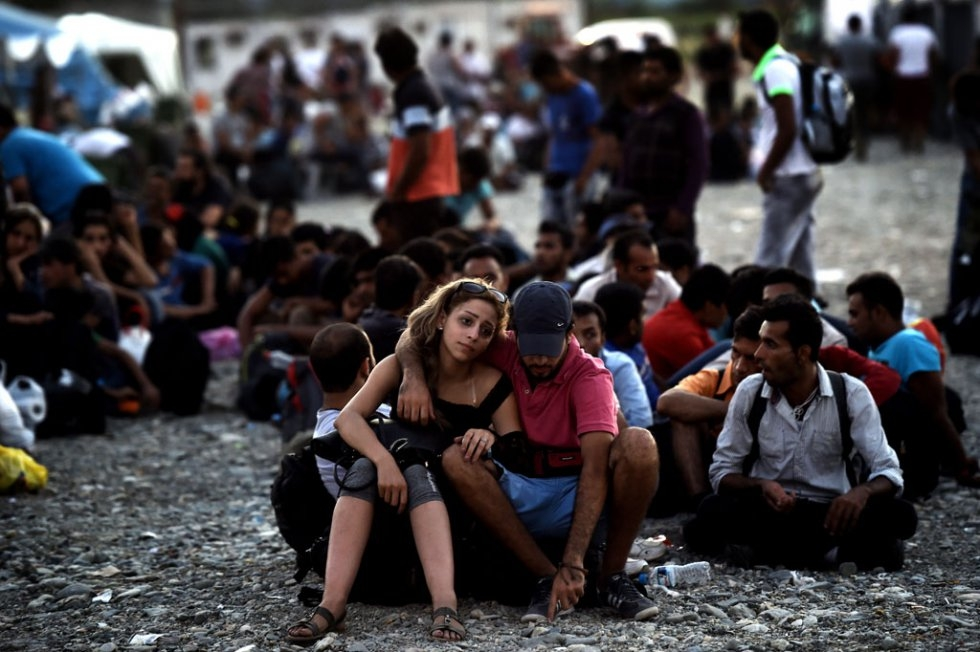 A Syrian couple waits with other migrants for the train near a train station in Gevgelija, Macedonia, on August 29, 2015