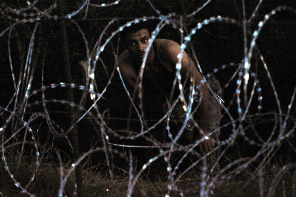 A migrant stands behind a blade iron fence at the Hungarian-Serbian border of Roszke village on August 30, 2015