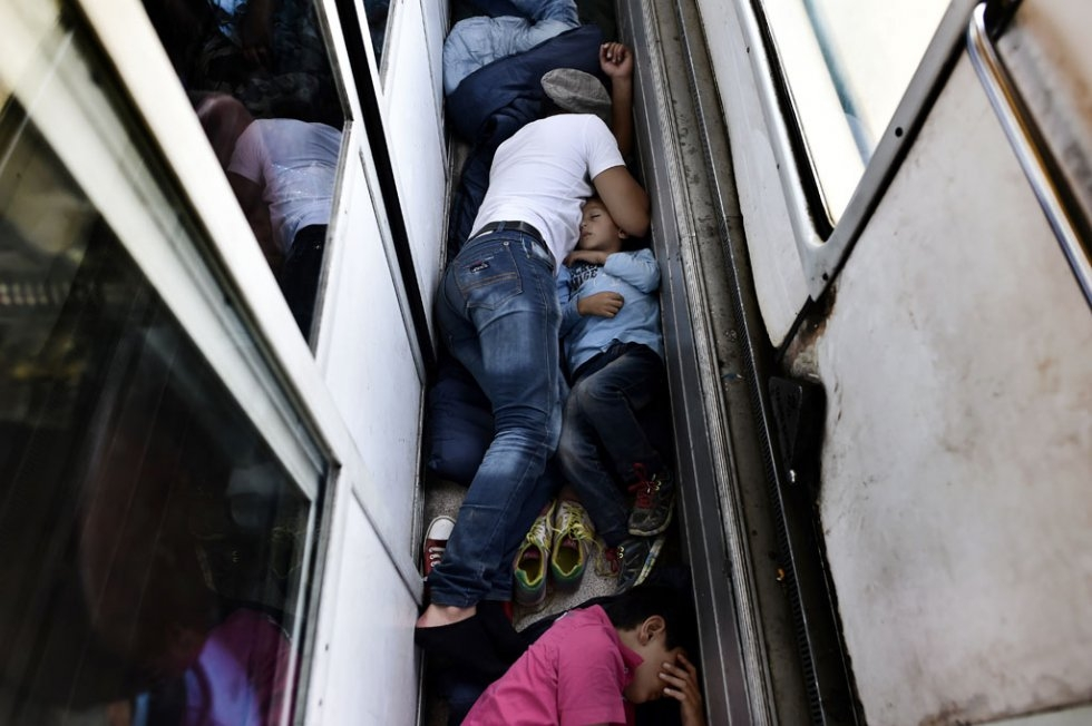 """Syrian refugees and migrants sleep on the floor of a carriage on a train from Macedonia to the Serbian border, on August 30, 2015"