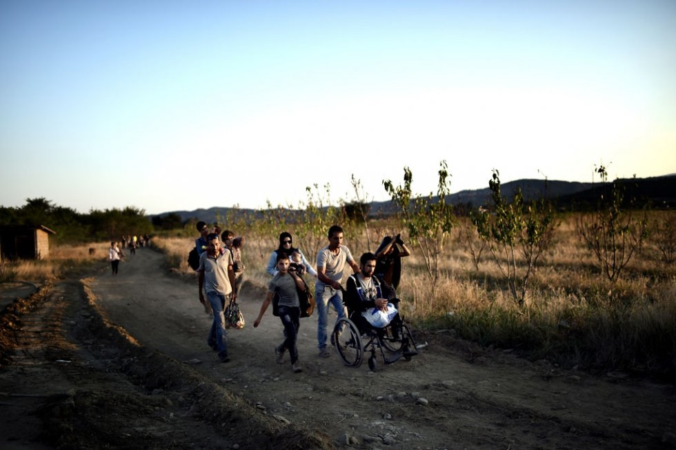 A Syrian man who lost his legs in a shelling near Damascus is helped by other migrants as they cross the border from Greece to Macedonia on August 29, 2015