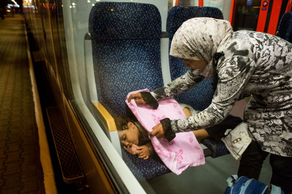 A migrant child sleeps on the train from Budapest to Vienna at the Austrian - Hungarian border in Hegyeshalom on August 31, 2015