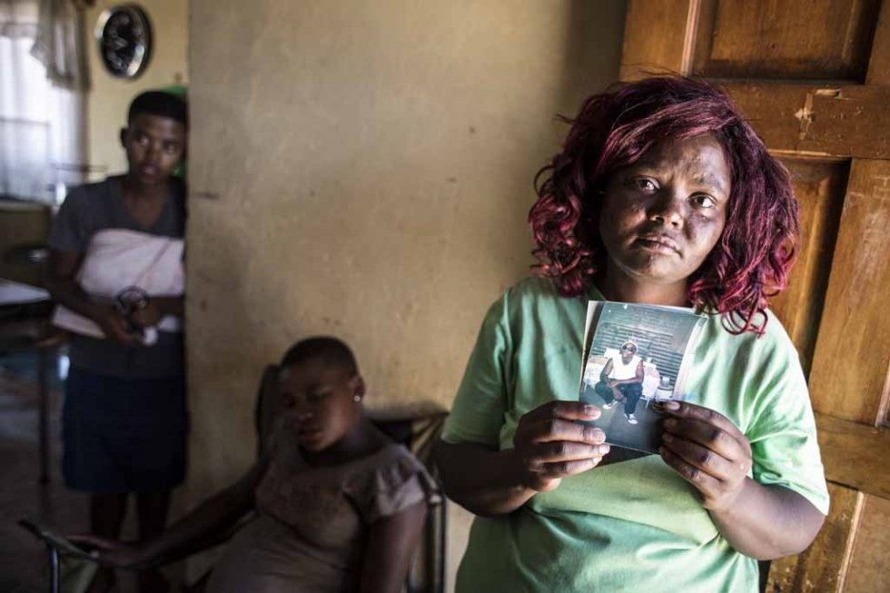 Seun Tangasha's sister holds up a photo of him. February 12, 2016.