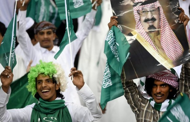 Saudi fans carry a portrait of King Abdullah bin Abdul Aziz al-Saud before the final of the 22nd Gulf Cup