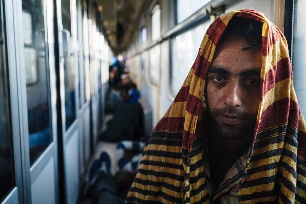 A Pakistani migrant travels on a train bound for Belgrade, early on July 18, 2015