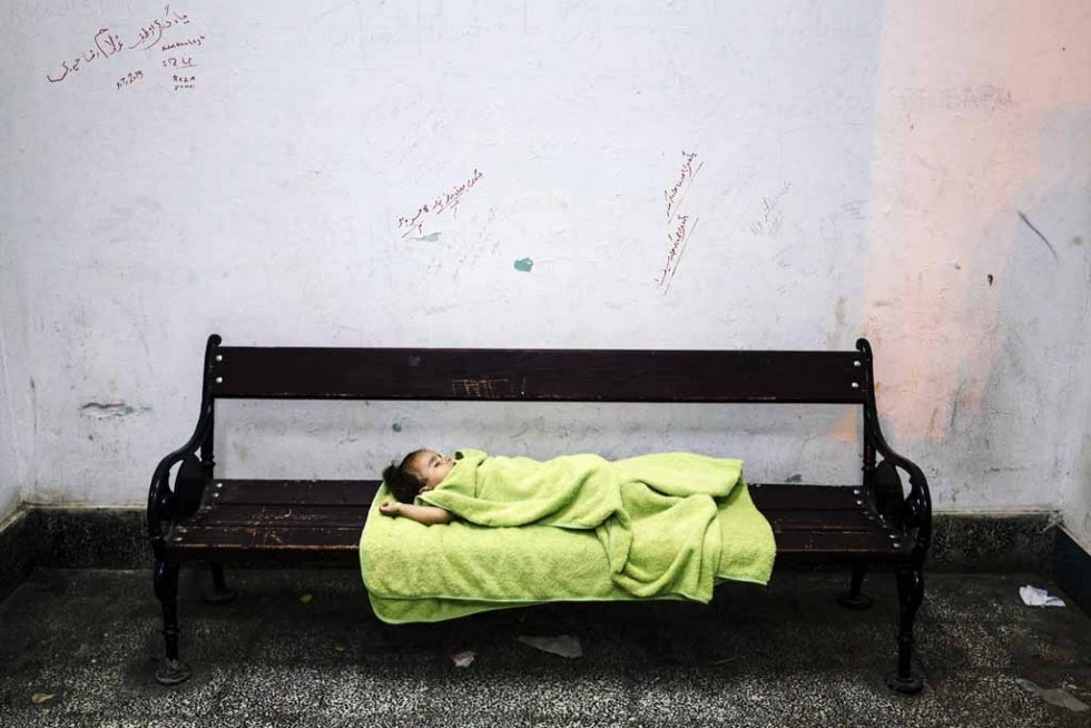 The baby of Syrian migrants sleeps in the waiting room of the train station of the southern Serbian town of Presevo, near the border with Macedonia on July 16, 2015 (AFP PHOTO / DIMITAR DILKOFF)