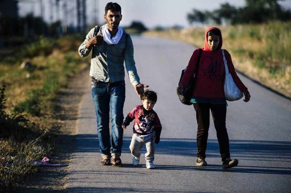 A migrant family walks on a road near Presevo on July 15, 2015