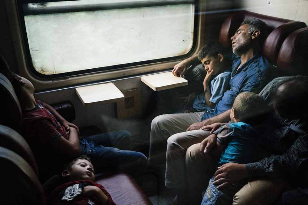 Migrants sleep on a train heading north from Nis to Belgrade, early on July 18, 2015