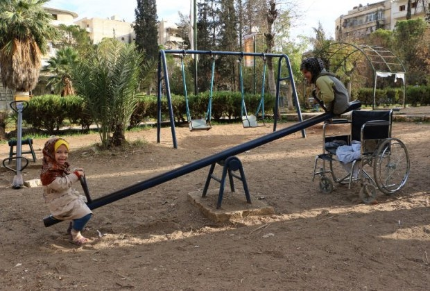 Shuruq (R), a nine-year old Syrian girl without legs, plays on a swing with another child in a park in the northern Syrian city of Aleppo on November 3, 2014 (AFP Photo / Baraa Al-Halabi)
