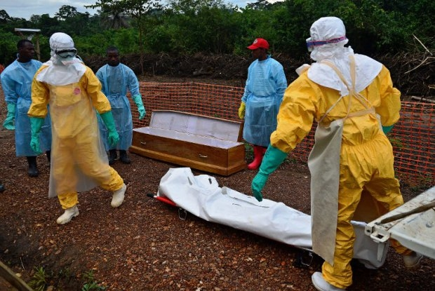 MSF medical workers carry the body bag of an Ebola victim in Kailahun, on August 14, 2014