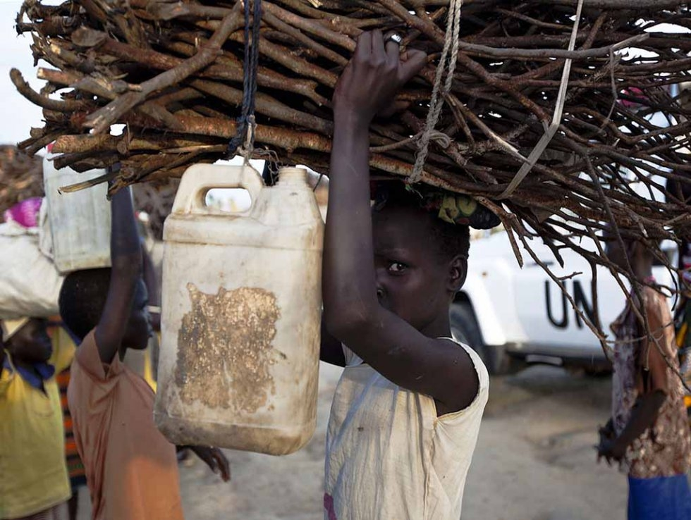 A young woman carries firewood at a UN base outside Bentiu. (AFP/Tristan McConnell)