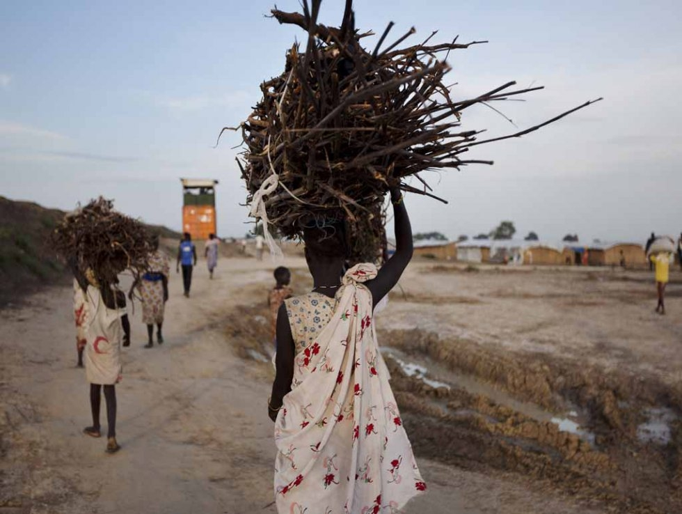Young women carry firewood at a UN base.
