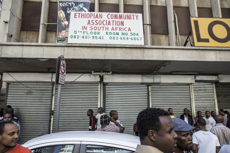 Foreigners stand in front of closed foreign-owned stores in Johannesburg on April 15, 2015