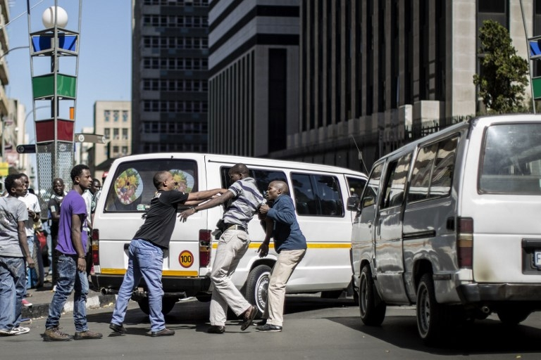 A South African taxi driver is pushed around by immigrants after making xenophobic remarks during a traffic incident in Johannesburg on April 15, 2015