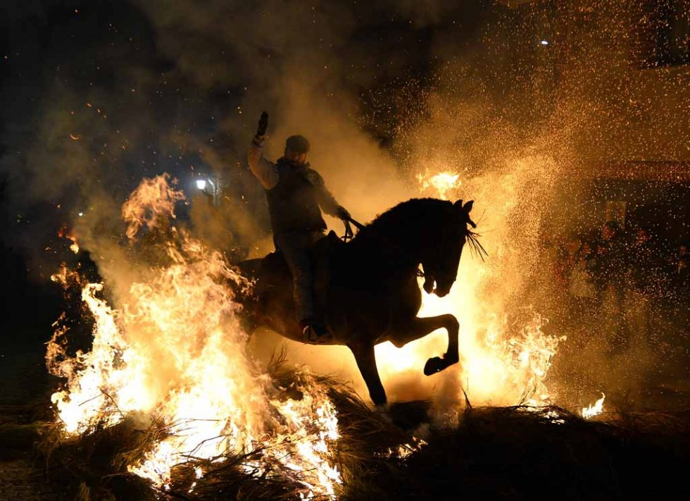 A rider guides his horse through flames during celebrations of the Feast of St. Anthony.