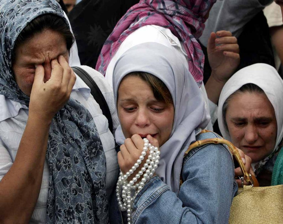 Bosnian Muslim women cry during a funeral of the remainds of their relative, victum of the Srebrenica massacre in the village of Potocari, 11 July 2005