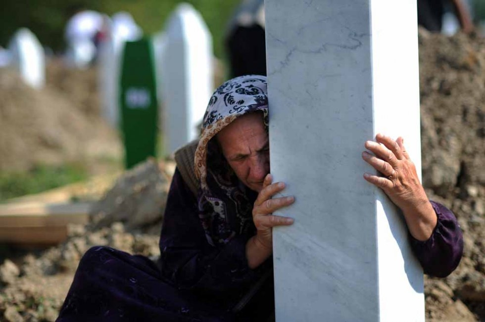 A Bosnian woman embraces a grave stone during a mass burial of 775 newly identified victims of the 1995 Srebrenica massacre at the Potocari memorial cemetery near Srebrenica on July 11, 2010 (AFP PHOTO / DIMITAR DILKOFF)