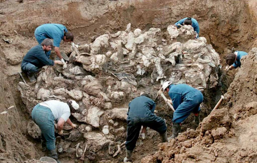 ICTY investigators work on top of a cluster of bodies, many of them with their hands tied in the back and blindfolded, at a mass grave outside Pilica, some 55 km east of Tuzla on 18 September, 1996