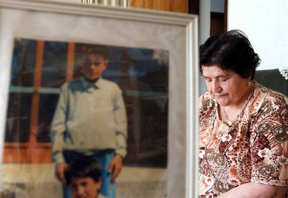 Bosnian Muslim Nura Alispahic, formerly of Srebrenica, is shown at her home in Tuzla on 04 June 2005 beside a picture of her son who was shot dead by Serb forces 10 years earlier