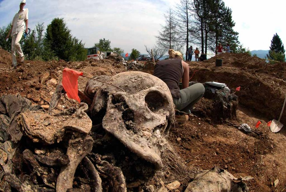 Forensic experts work in a mass grave in the village of Budak, near Srebrenica, 09 July 2005