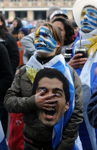 A Uruguayan woman sings the national anthem in Montevideo as Uruguay-Colombia match is broadcast live, June 28, 2014.