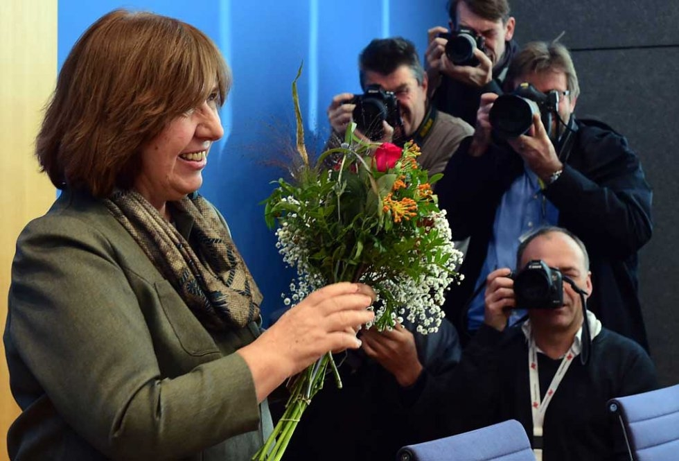 The laureate of the 2015 Nobel Literature Prize, Belarussian writer and dissident Svetlana Alexievich, receives a bunch of flowers from well-wishers prior to a press conference in Berlin, on October 10, 2015