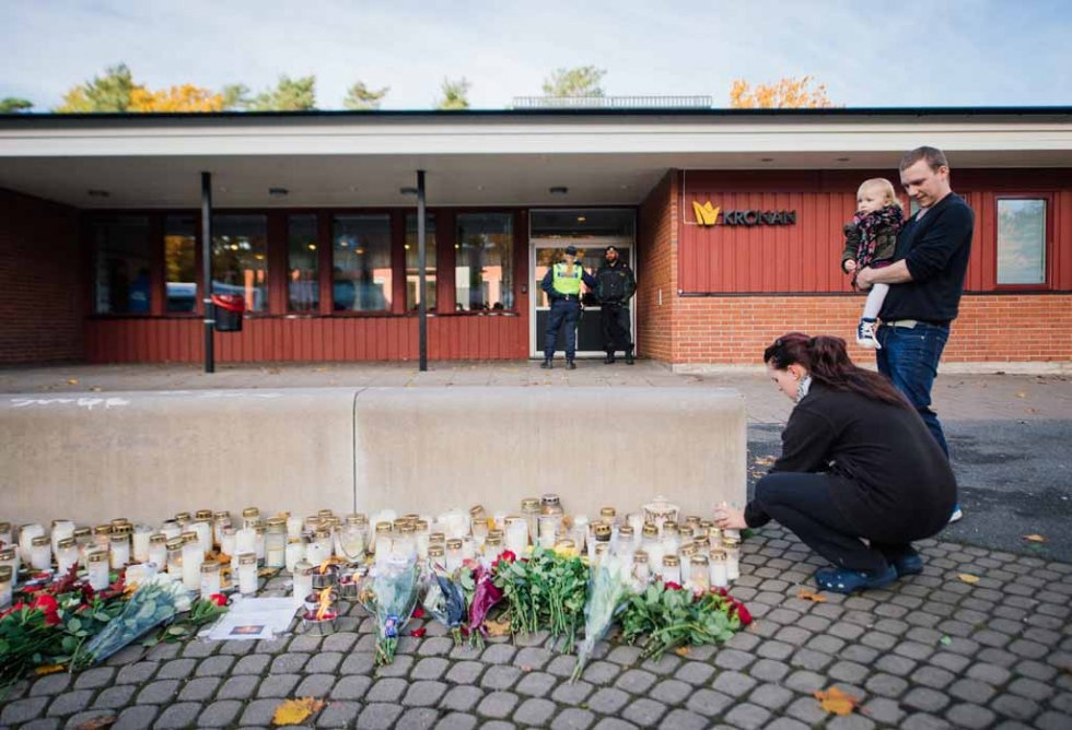 A woman lights a candle outside the school after the attack.