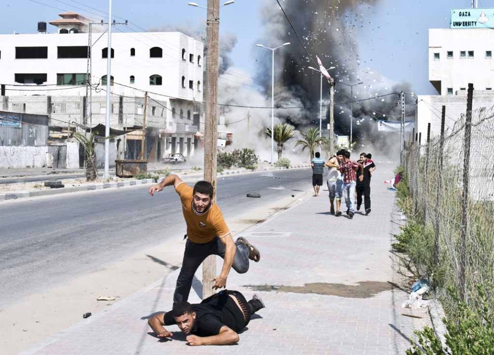 Palestinians scramble after an air strike on a house in Gaza. August, 2014.