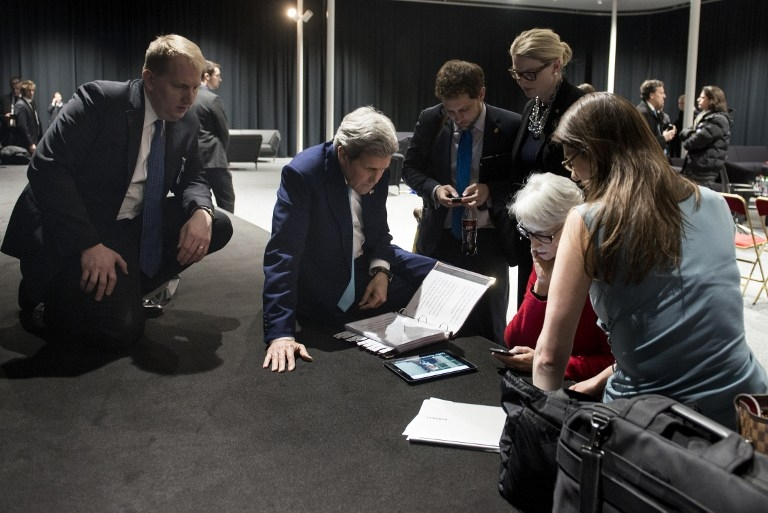 US Secretary of State John Kerry watches on a tablet device as US President Barack Obama addresses the nation after the end of Iran nuclear talks in Lausanne on April 2, 2015