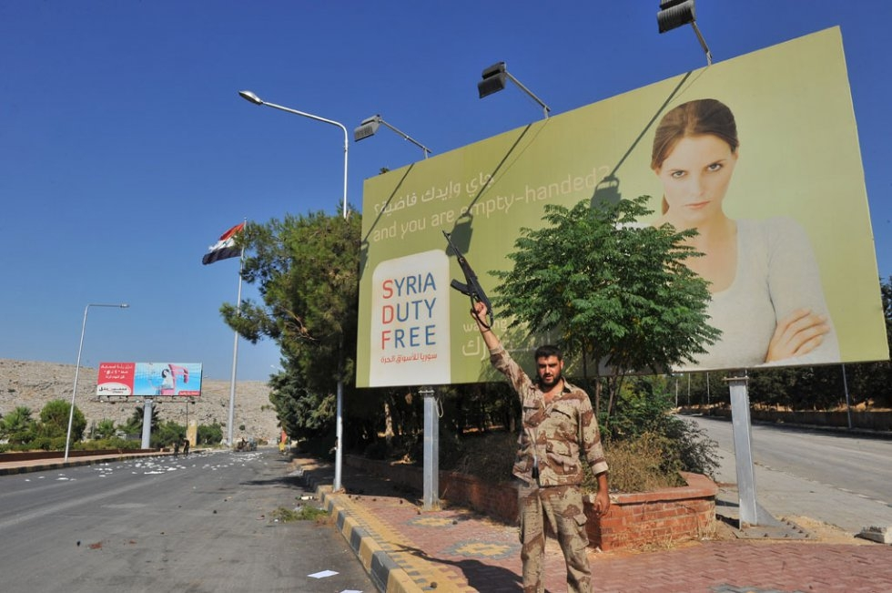 A Syrian rebel poses in front of a sign at the Bab al-Hawa border crossing with Syria. July, 2012.