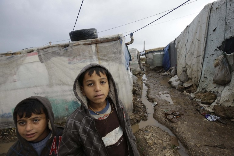 Syrian refugees at a camp damaged by a storm in Akkar, north Lebanon on January 7, 2015
