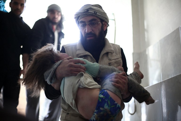 A man carries a wounded child at a makeshift clinic in Douma, Syria on February 5, 2015