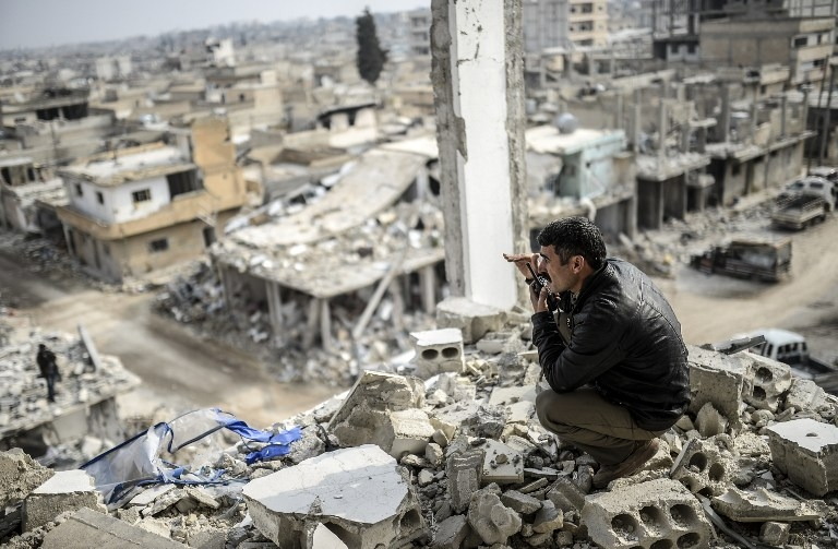A Kurdish man talks with a radio as he checks the eastern part of Kobane, Syria on January 28, 2015