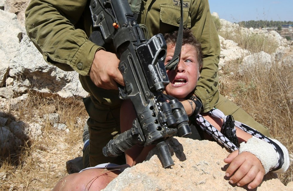 An Israeli soldier controls a Palestinian boy during clashes in the West Bank village of Nabi Saleh on August 28, 2015 (AFP Photo / Abbas Momani)