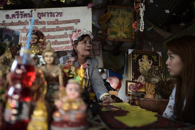 A fortune teller at a Bangkok shrine to the ghost 'Nak' on January 15, 2015