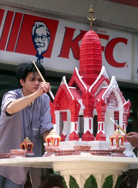 A worker paints a spirit house for the Thai New Year in 1999