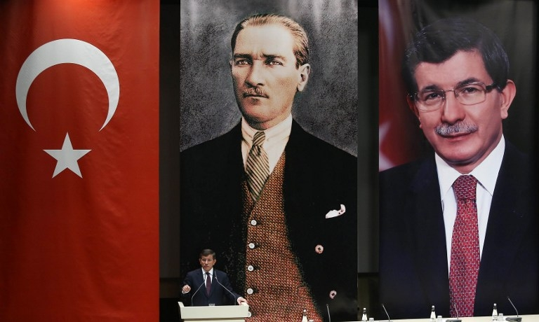 Turkish Prime Minister Ahmet Davutoglu delivers a speech below portraits of himself and Mustafa Kemal Ataturk, the founder of modern-day Turkey, in Ankara on May 20, 2015