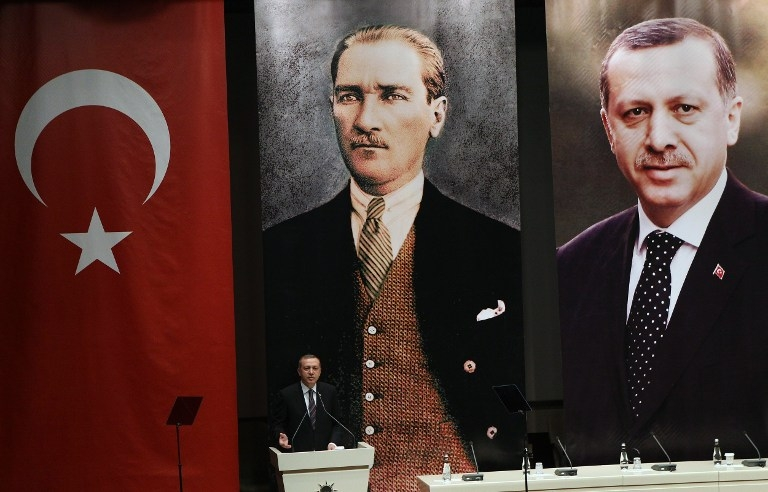 Turkey's then prime minister Recep Tayyip Erdogan delivers a speech in front of posters of himself and Mustafa Kemal Ataturk, the founder of modern Turkey, at a meeting of the ruling AKP party in Ankara on June 25, 2014