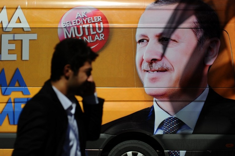A Turkish man talks on the phone in front of a poster of Recep Tayyip Erdogan in Istanbul on March 21, 2014, after the then premier said he would eradicate Twitter in response to corruption allegations targeting his inner circle