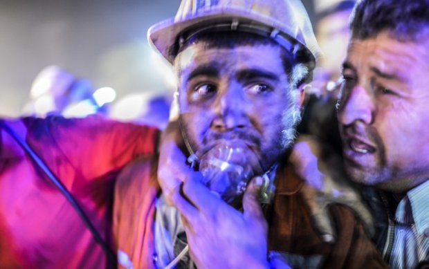 A miner recovers alongside his father after emerging from the Soma mine