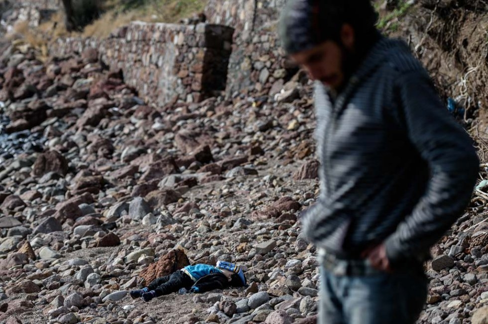 A man stands next to the body of a migrant child washed up on a beach in Canakkale's Bademli district on January 30, 2016 (AFP / Ozan Kose)