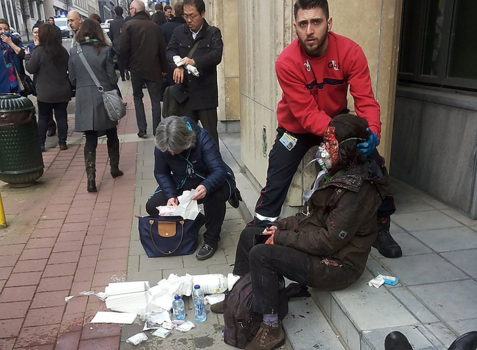 A private security guard helps a wounded woman outside the Maalbeek - Maelbeek metro station in Brussels on March 22, 2016 (AFP / Michael Villa)