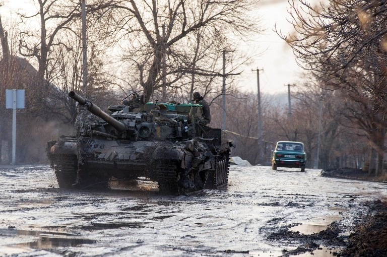 An armoured vehicle pulls an Ukrainian T-72 tank after it was damaged during combat in the villige of Horlivka on February 4, 2015